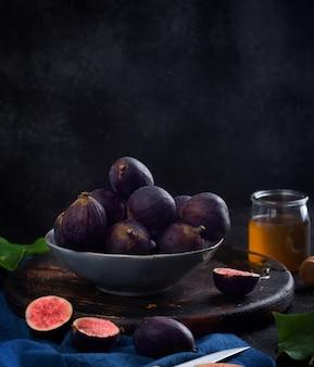 Figos frescos em uma mesa de madeira escura com mel e hortelã