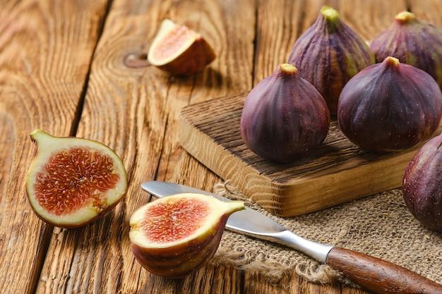 Figos frescos, inteiros e cortados em rodelas na mesa de madeira