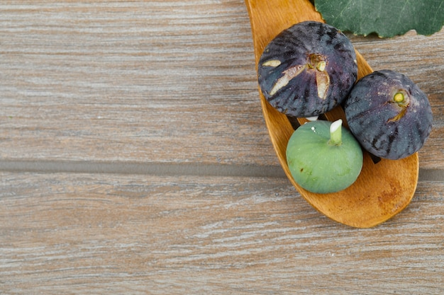 Figos frescos maduros com uma colher de pau na mesa de madeira.