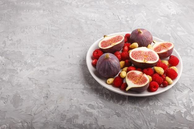Figos frescos, morangos e framboesas na chapa branca em concreto cinza. vista lateral