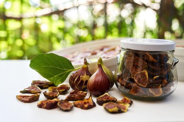Figos frescos repousam na mesa ao lado de figos secos em uma jarra de vidro