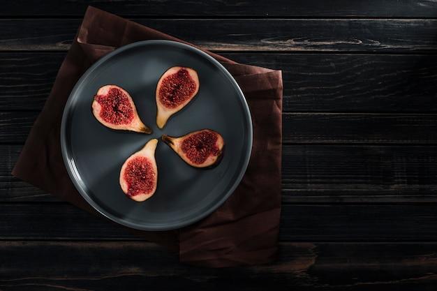 Figos frescos são inteiros e cortados em fatias no prato em uma chave baixa