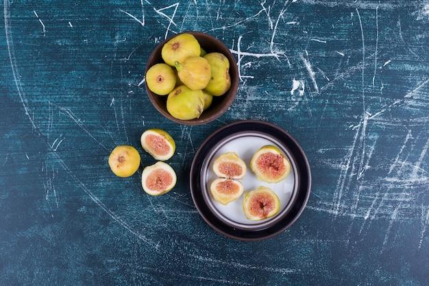 Figos inteiros e fatiados em pratos de madeira no meio.