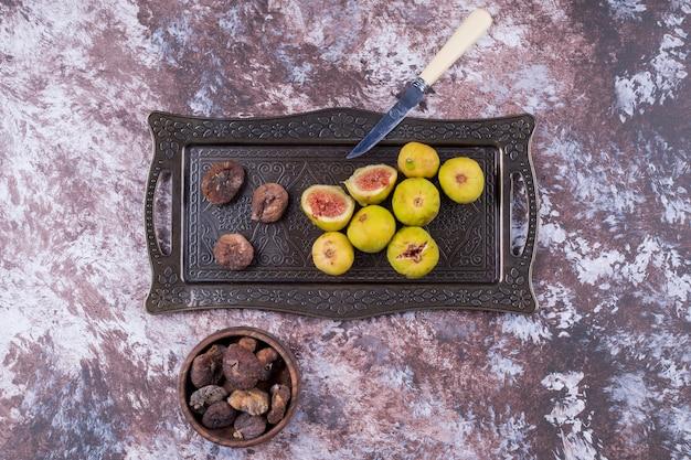 Figos inteiros secos e fatiados em tabuleiro metálico e em chávena de madeira ao centro.
