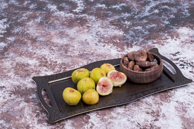 Figos inteiros secos e fatiados em tabuleiro metálico e em chávena de madeira, vista de ângulo.