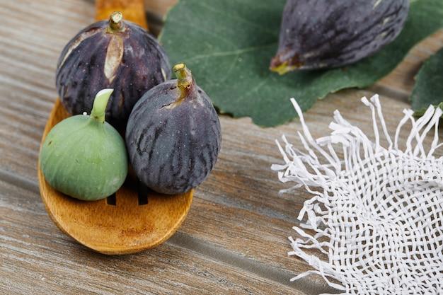 Figos maduros com uma colher de pau na mesa de madeira.