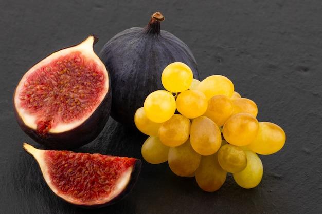 Figos maduros frescos e uvas no escuro