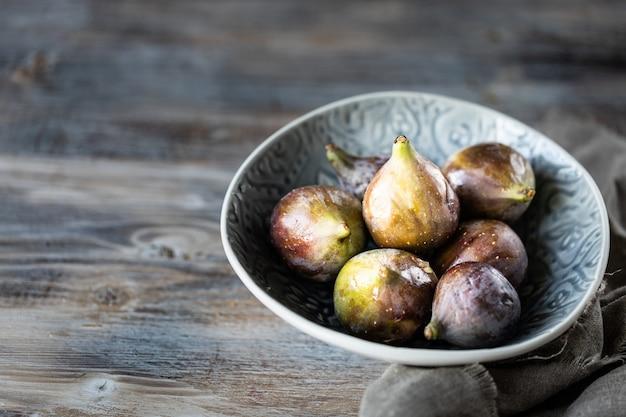 Figos maduros frescos em uma tigela sobre uma mesa de madeira escura
