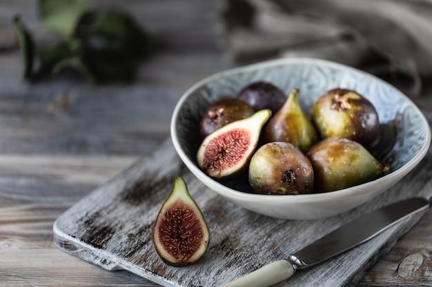 Figos maduros frescos em uma tigela sobre uma mesa de madeira escura.