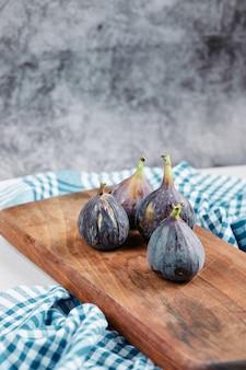 Figos na placa de madeira com uma toalha de mesa azul.