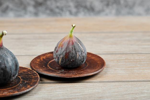 Figos no prato pequeno e na mesa de madeira.