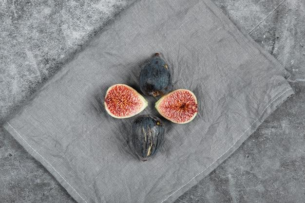 Figos pretos maduros sobre um fundo de mármore com uma toalha de mesa cinza. foto de alta qualidade