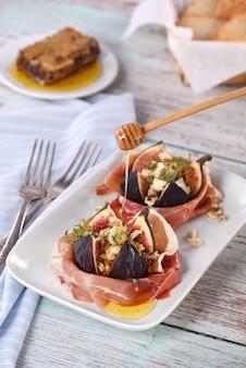 Figos recheados com queijo azul, embrulhados em presunto de parma, regados com mel