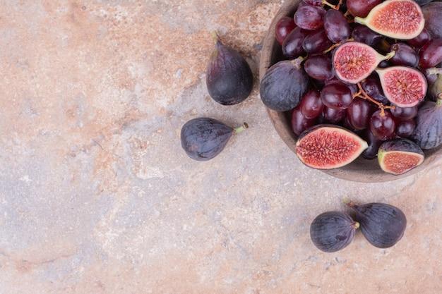 Figos roxos e bagas de cornel em um copo de madeira