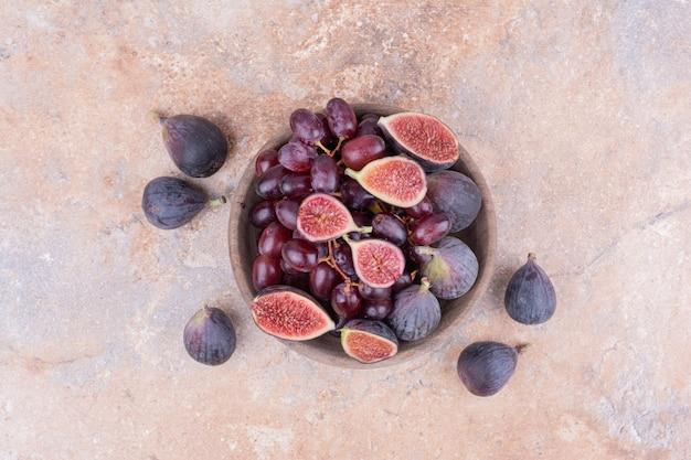 Figos roxos e cornelas vermelhas em uma xícara de madeira