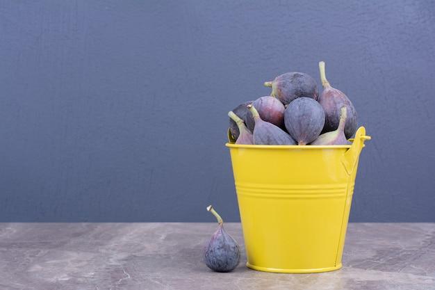 Figos roxos em um balde metálico amarelo