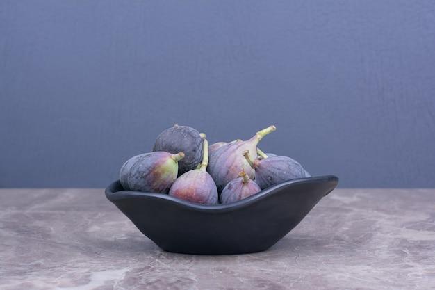 Figos roxos isolados em um pires de cerâmica preta
