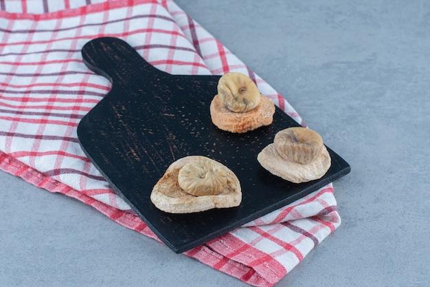 Figos secos na tábua de cortar, na toalha, no pano de prato, na mesa de mármore.