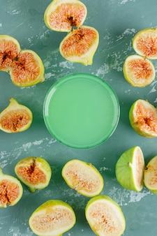Figos verdes com copo de bebida na parede de gesso, vista superior.