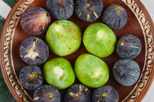 Figos verdes e pretos em um prato de cerâmica, close-up