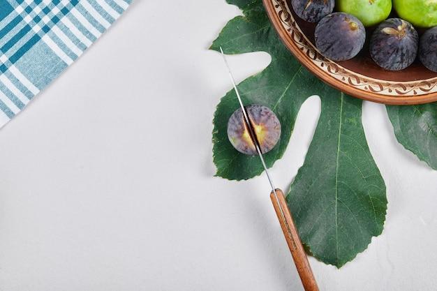 Figos verdes e pretos em um prato de cerâmica com uma faca e uma folha