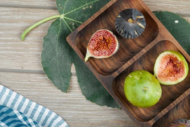 Figos verdes e pretos maduros em travessa de madeira com uma folha e uma toalha de mesa.