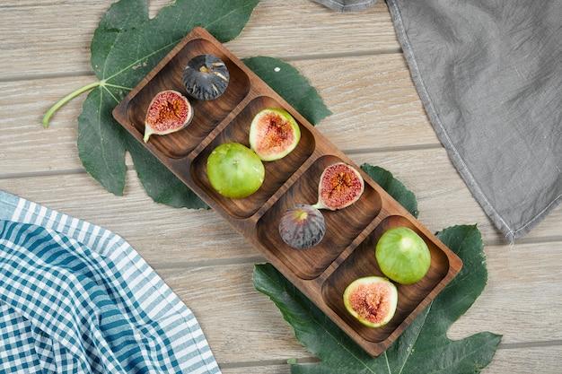 Figos verdes e pretos maduros em uma travessa de madeira com uma folha e toalhas de mesa.