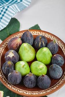 Figos verdes e pretos num prato de cerâmica. foto de alta qualidade