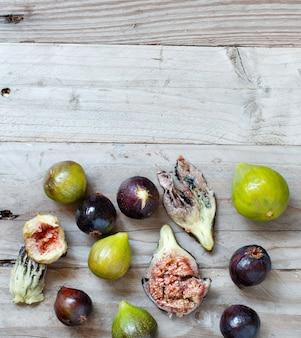 Figos verdes e roxos em superfície rústica de madeira