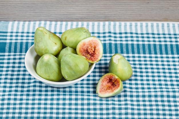 Figos verdes em uma tigela branca e sobre uma mesa de madeira com toalha de mesa azul. foto de alta qualidade