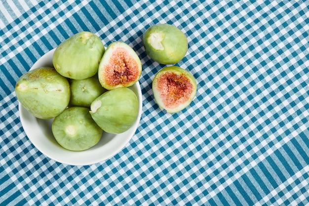 Figos verdes em uma tigela branca e sobre uma toalha de mesa azul. foto de alta qualidade