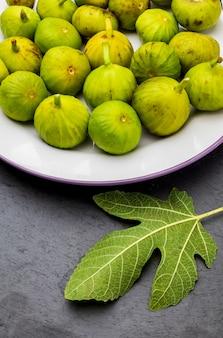 Figos verdes, frescos e maduros. com uma folha de figueira.