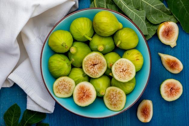 Figos verdes inteiros e cortados, com folhas de figo. primeiro plano.