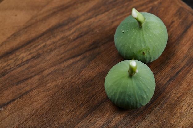 Figos verdes maduros na mesa de madeira.