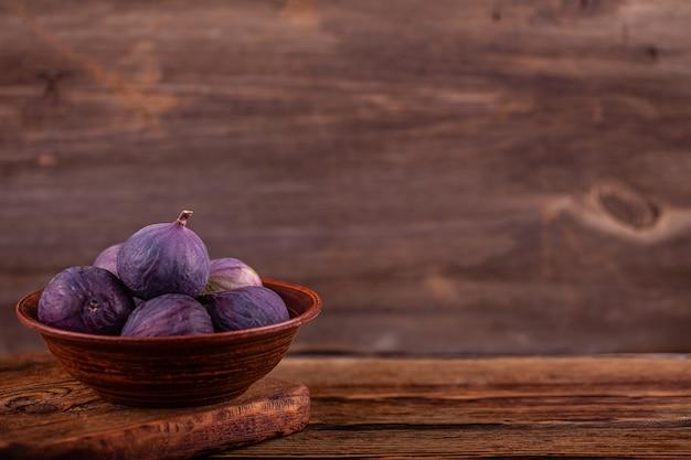 Figos violetas doces maduros na tigela vintage, mesa de madeira, conceito de doces vegan