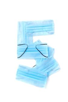 Figura 5, cinco feitas à mão de máscaras faciais protetoras azuis médicas antibacterianas em uma parede branca, espaço de cópia tipo de letra criativo para criar novas informações numéricas.