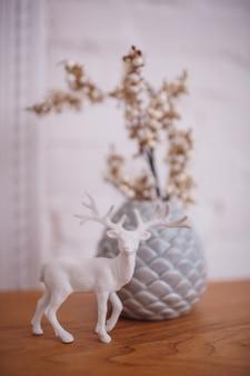 Figura branca de um veado está diante de um vaso