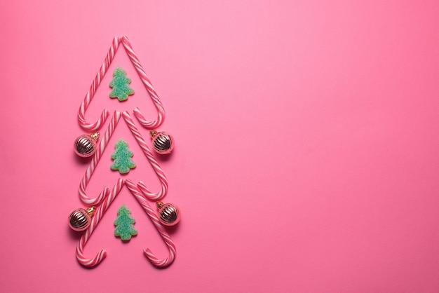 Figura da árvore de natal feita de doces e bolas decorativas em um fundo rosa, vista superior. conceito de natal e ano novo