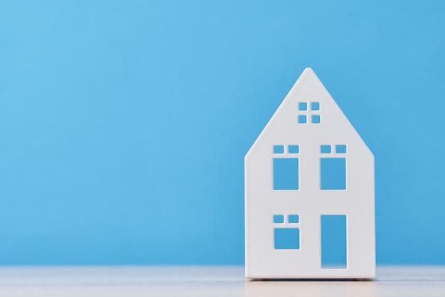Figura da casa de brinquedo na parede azul com espaço de cópia