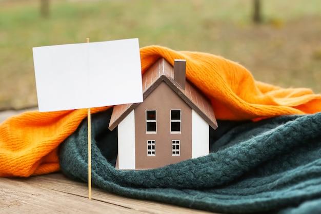 Figura da casa, manta, lenço e folha de papel em branco na vara ao ar livre. conceito de estação de aquecimento