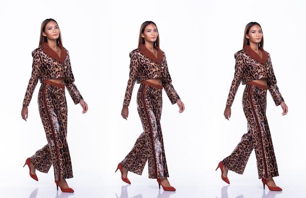 Figura de comprimento total de jovem mulher asiática bronzeada pele alta moda usa vestido padrão de pele de cobra e sapatos de salto alto ambulantes. iluminação de estúdio com fundo branco isolado, conceito de pacote de grupo de colagem