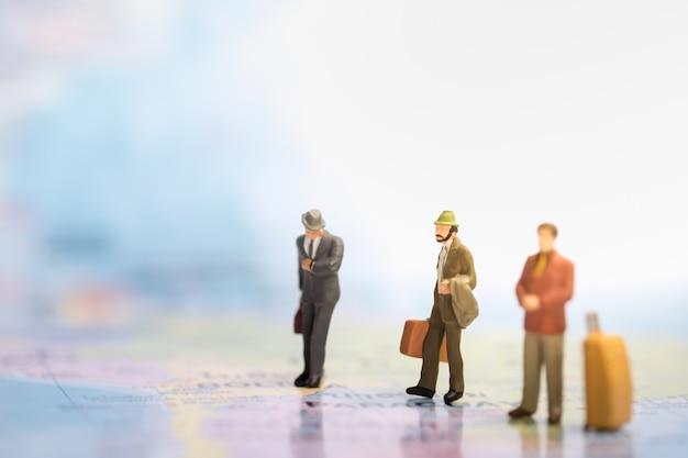 Figura de empresário em miniatura com mala e bagagem andando e em pé e olhar um relógio no mapa do mundo.