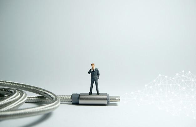 Figura de empresário em pé no cabo usb