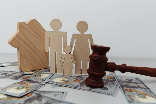 Figura de família com martelo de juiz e casa em notas de dólar proteção familiar ou conceito de lei