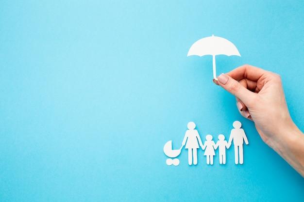 Figura de família e mão segurando a forma de guarda-chuva