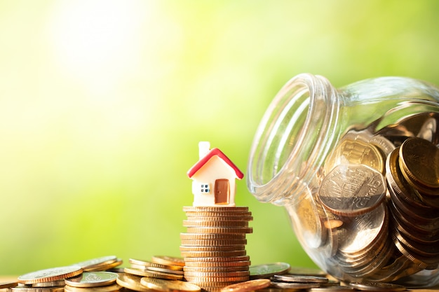 Figura de forma de casa vermelha na pilha e pilha de moedas