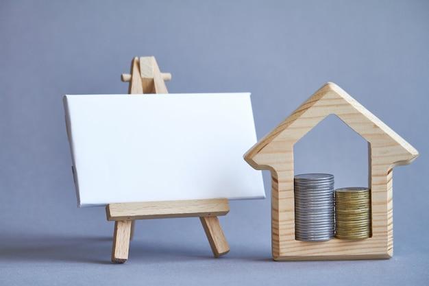 Figura de madeira da casa com duas colunas de moedas dentro e quadro branco