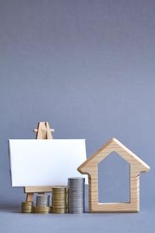 Figura de madeira da casa com várias colunas de moedas nas proximidades e quadro branco