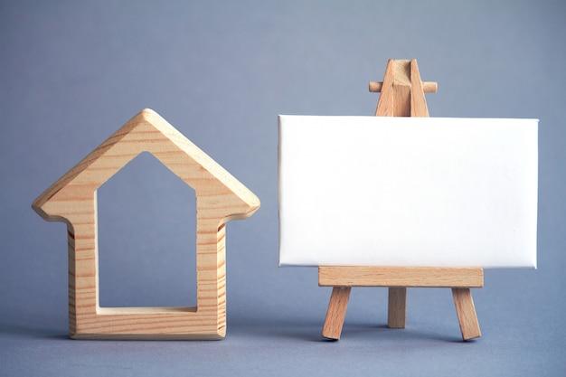 Figura de madeira da casa e quadro branco em cavalete em miniatura em cinza