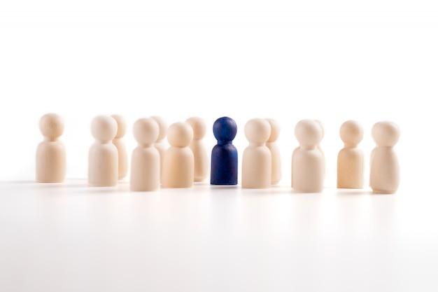 Figura de madeira em pé com a equipe para mostrar influência e empoderamento.